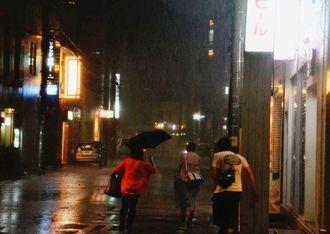 急に雨風が強まり、居酒屋から出た人は傘もささず目的地まで駆け抜けた=11日午後10時前、石垣市美崎町