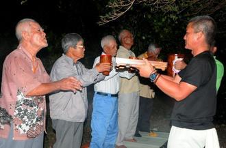 「ヒーヤ、ヤッカ、ヤッカ、ヤッカ」とはやしを立てながら神酒を酌み交わす男性たち=5日夜、多良間村仲筋