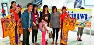 ジェットスター・アジアの沖縄初就航を歓迎し、到着客に記念品をプレゼントした=20日、那覇空港国際線ターミナル(OCVB提供)