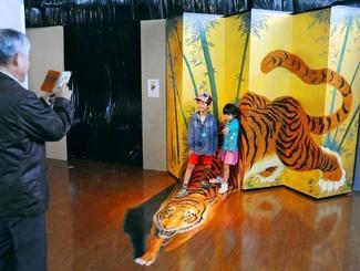豊見城市豊崎・沖縄アウトレットモールあしびなーで開催中の「ふしぎの迷宮!トリックアート展あしびなーの巻」。絵の近くでトリックアートを体感する来場者