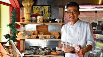 「ハムやソーセージに合う手作りパンもそろえています」と話す店長の吉田和彦さん=浦添市牧港
