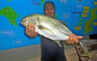 恩納村海岸で64・5センチ、2・82キロのオニヒラアジを釣った佐久川亮さん=7月27日