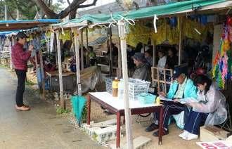 集会で新基地建設反対の声を上げる市民=16日、名護辺野古・キャンプ・シュワブゲート前