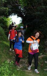 険しい下り坂の「緑のトンネル」を抜け満面の笑顔=29日、うるま市・勝連城跡