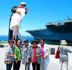 彫像と航空母艦をバックに記念撮影する山内繁子部長(左から2人目)ら=米サンディエゴ