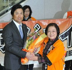 城間幹子市長から花束を受け取る高橋由伸新監督(右)=15日午前11時21分、那覇空港