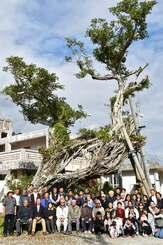 大浦のシンボルとして愛されてきたガジュマルと記念撮影をする区民たち=4日、名護市・大浦区公民館前