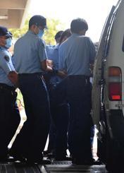 署員に抱えられ護送車に運び込まれる容疑者=18日午後2時28分、那覇署