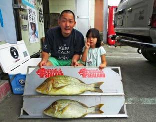 玉城海岸で68センチ、3.7キロと56.5センチ、2.15キロのタマンを釣った新垣直也さん(左)とルルちゃん=5月7日
