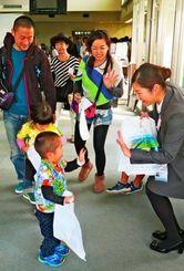 宮古-羽田線の就航を祝い職員(右)から記念品を受け取る利用客=27日午後、宮古空港