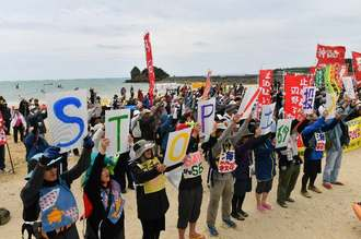 浜辺で土砂投入に抗議する市民ら=25日午後2時すぎ、名護市辺野古
