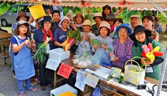 宮城島でつくった野菜を手に「たかはなり市」をアピールする島の住民ら=4日、うるま市・宮城島