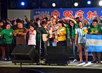 宜野座村まつりで「ギノザンチュ ヤイビン」を歌う伊芸研治さん(前列中央)ら=23日、同村農村公園