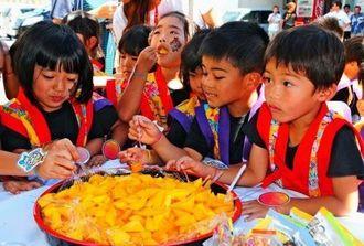 ことし初出荷される宮古島産マンゴーをほおばる花園保育所の園児たち=4日、市平良西里の宮古郵便局