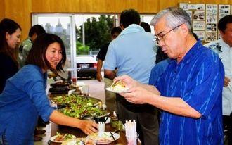 洋食風にアレンジされたヤギ料理の説明を受ける高良文雄町長(右)
