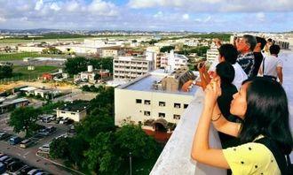 沖国大生の案内で、普天間飛行場を見学するシンポジウム参加者=12日午後、宜野湾市・沖縄国際大学