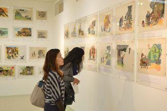 儀間さんの絵本作品の原画を熱心に見る来場者=29日、うるま市与那城伊計・旧伊計小中学校