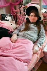 自宅のベッドで横になって取材に応じる女性=1日、岡山市