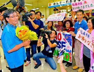 出迎えた支援者に笑顔を見せる稲嶺進名護市長(左)=24日午後9時26分、那覇空港