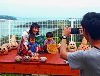 うれしそうに撮影する小澤さん家族=10月25日、今帰仁村・橋の駅リカリカワルミ