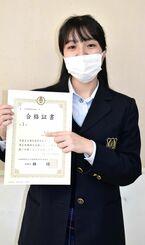 全商簿記1級の合格証を手に笑顔の太田夢々さん=2月、南風原高校
