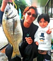 糸満海岸で42・5センチ、1・31キロのミナミクロダイを釣った南祥太さん(左)と琉空くん=20日