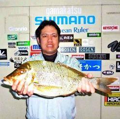 20日、宜野湾海岸で55センチ2・46キロのタマンを釣ったT・N・F・Cの井上慎吾さん。餌はシガヤーダコ