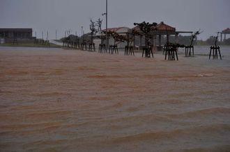 台風19号の接近と満潮時刻が重なり冠水する駐車場=11日午前8時51分、西原マリンパーク東ゲート
