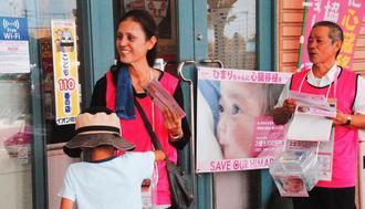 募金を呼び掛けるひまりちゃんの祖母の兼城信子さん(左)と夫の正昭さん=7月31日、うるま市・イオン具志川店