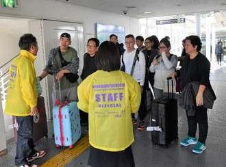 不発弾処理によるモノレールの一時全線運休を知らされ、引き返す外国人観光客=16日午前10時31分、那覇空港