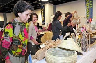 チガヤや月桃を使った籠バッグなどが並んだ展示即売コーナー=28日、那覇市久茂地・タイムスギャラリー