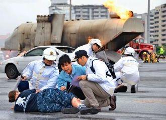 米軍機事故を想定した負傷者救助の訓練を行う県警職員ら=24日、那覇軍港