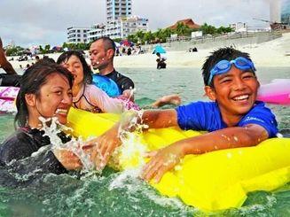 水遊びで暑さをしのぐ家族連れ=21日午後4時ごろ、北谷町・アラハビーチ(国吉聡志撮影)