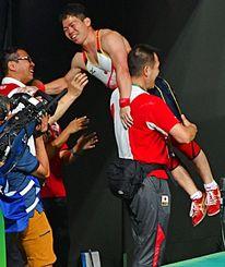 日本新記録となるジャーク169キロを成功させ、セコンドに抱き上げられる糸数陽一選手=リオデジャネイロ(又吉俊充撮影)