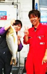 宜野湾海岸で64・2センチ、2・82キロのタマンを釣った當山富貴子さん(左)=5月30日