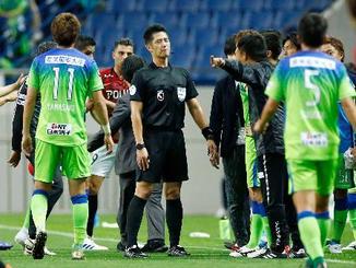 17日のJ1浦和―湘南戦で、湘南のゴールを得点と認めず選手らの抗議を受ける山本雄大主審(中央)=埼玉スタジアム
