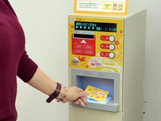 「オキカ」チャージ機の実演をする沖縄ICカードの担当者=10日、琉銀本店内