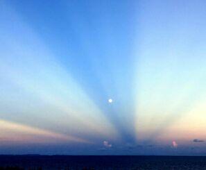 西の空に見えた「反薄明(はくめい)光線」と月=22日午前6時15分ごろ、町砂辺(読者提供)