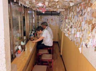 店内の様子です。カウンターが8席ほど。壁も天井もすごい名刺の数。