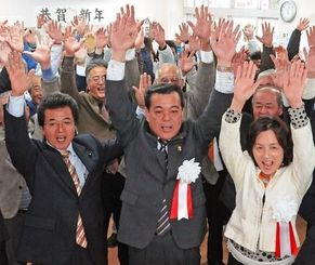 無投票当選が決まり、支援者とともに万歳する古謝景春氏(前列中央)と敬子夫人(同右)=19日午後5時すぎ、南城市佐敷の後援会事務所