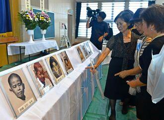 犠牲者の遺影に見入る慰霊祭出席者=30日午前11時55分、うるま市石川・宮森小学校(田嶋正雄撮影)