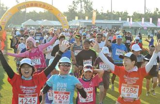 朝日を浴びてスタートするフルマラソンの出場者=25日午前7時半すぎ、久米島町営仲里野球場(伊藤桃子撮影)
