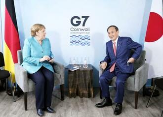 ドイツのメルケル首相(左)と会談する菅首相=12日、英コーンウォール(代表撮影・共同)