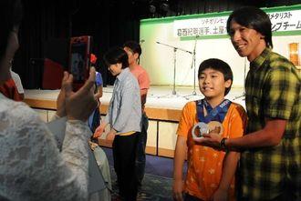子どもにメダルを掛け、記念撮影に応じる葛西紀明さん=13日、宮古島市内のホテル