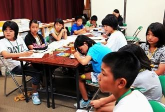 南風原の学童疎開70周年を記念した子ども平和交流事業で、現地研修に向け事前学習する小学生たち=7日、南風原町立南風原文化センター
