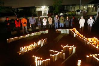 熊本地震の「本震」から3年を迎えた熊本県益城町の木山仮設団地で、地震の発生時刻に合わせ黙とうする住民ら=16日午前1時25分