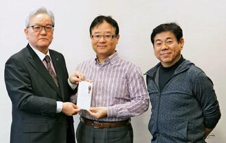 沖縄タイムス社の武富和彦社長(左)に寄付金を手渡す久高学さん(中央)と藤木勇人さん=30日、同社