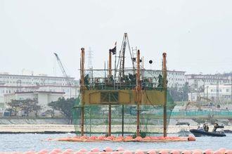 スパット台船から掘削棒が海面に下りていくのが確認された=12日午後2時28分、名護市辺野古沖
