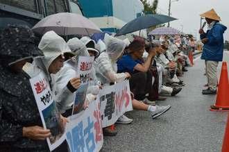 雨の中、埋め立てに抗議する市民ら=26日、名護市辺野古、米軍キャンプ・シュワブのゲート前