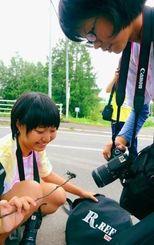 見つけたカブトムシを接写する真和志の中西佐和さん(左)と田渕綾菜さん=6日、北海道美瑛町(田嶋正雄撮影)